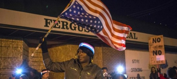 A woman holds an upside-down American flag from a moving vehicle as she takes part in a protest near the Ferguson Police Station in Ferguson, Missouri November 29, 2014. Ferguson, a predominantly black city of about 21,000 people where almost all the political leaders and police are white, became the focal point of a national debate on race relations after police officer Darren Wilson shot and killed Michael Brown on August 9.   REUTERS/Adrees Latif  (UNITED STATES - Tags: CIVIL UNREST POLITICS TPX IMAGES OF THE DAY)