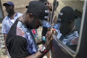 Mourner Tramell Metz pauses at the hearse of Samuel Dubose before his casket is transported to a cemetery during funeral services at the Church of the Living God in the Avondale neighborhood of Cincinnati, Tuesday, July 28, 2015. Dubose was fatally shot by a University of Cincinnati police officer who stopped him for a missing license plate. (AP Photo/John Minchillo)