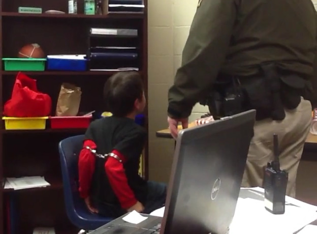 In this image made from video taken in August 2014, and provided by the American Civil Liberties Union on Tuesday, Aug. 4, 2015, an 8-year-old boy struggles and cries out as he sits in a chair with handcuffs around his biceps and his arms locked behind him while a school resource officer stands nearby, at an elementary school in Covington, Ky. The boy's mother, along with the mother of a 9-year-old girl who was also handcuffed at the school, have filed a federal lawsuit against the school. The lawsuit says both children have attention deficit hyperactivity disorder, and school officials are aware of their disabilities. (American Civil Liberties Union via AP)
